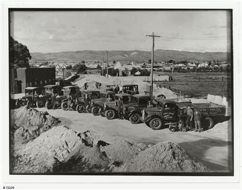 Row of trucks and men at a quarry or plant • Photograph